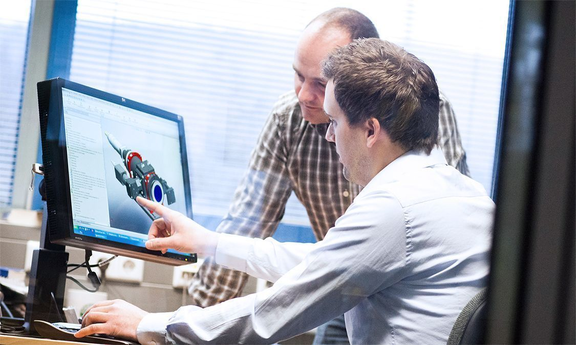 Two people looking at a CAD drawing on the screen